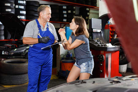 Young woman pleading male mechanic at auto service to repair her car