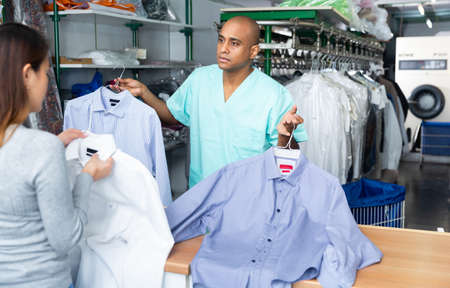Man dry-cleaning worker giving clothes to customer