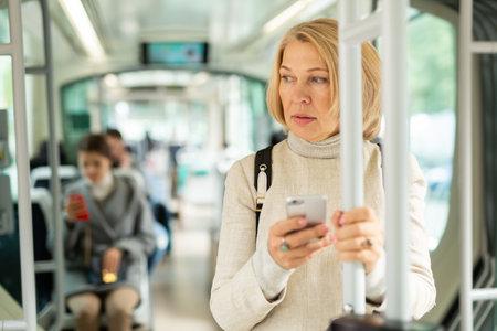 Portrait of female passenger using mobile phone in tram