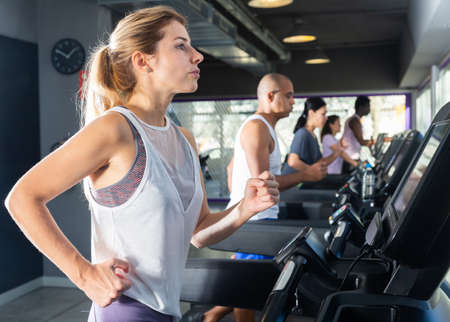 Focused woman training on treadmill in gy