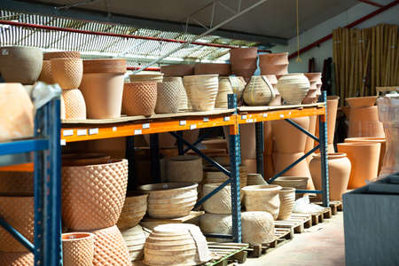 Rows with clay pots for plants in garden store
