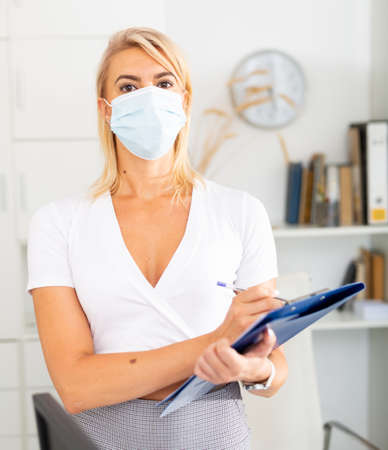 Female office worker in protective mask is standing with documents before signing it in office