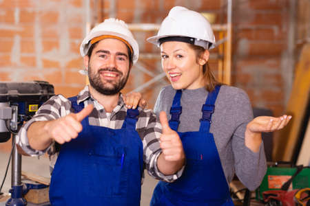 Two professional builders with thumbs up