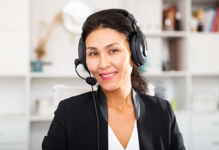 Smiling young female operator talking with customer using headset at office