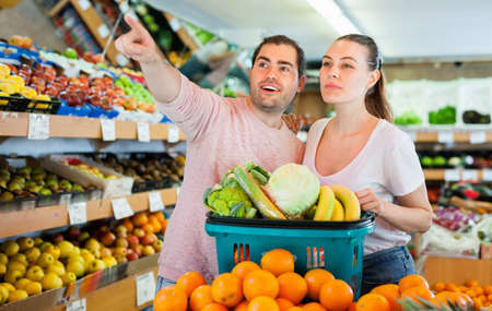 Positive family couple standing with full cart after shopping and pointing to shelves in fruit store