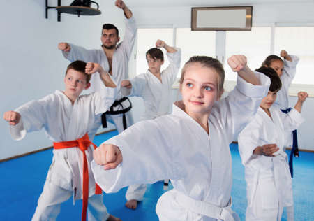 Children training karate moves at karate class