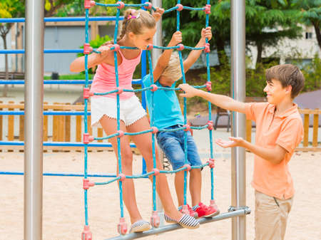Kids are climbing on the grid on the playground. Zdjęcie Seryjne