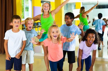 happy tweenagers with choreographer in modern dance studio