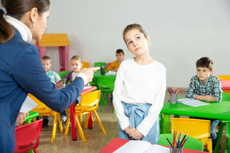 Upset schoolgirl listening reprimanding of teacher