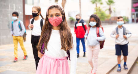 Tween schoolgirl in protective mask going to college on fall day