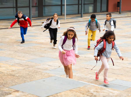 Tween boys and girls with school backpacks running in schoolyard