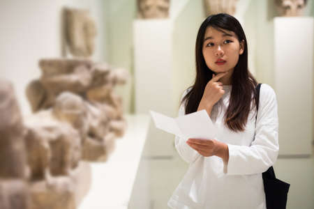 Chinese woman visitor with guide book looking at exhibition in museum