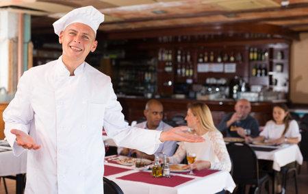 Chef in uniform invites to visit restaurant