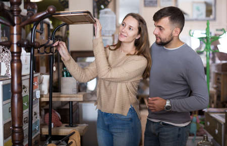 Couple looking for hallstand in shop