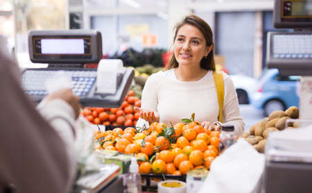 Customer selects ripe tangerines on counter