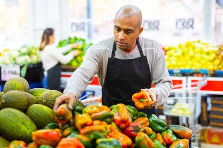 Supermarket worker in black apron putting vegetables