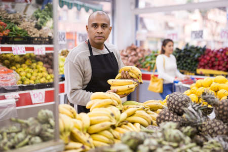 Friendly grocery store employee lays ripe bananas on counter