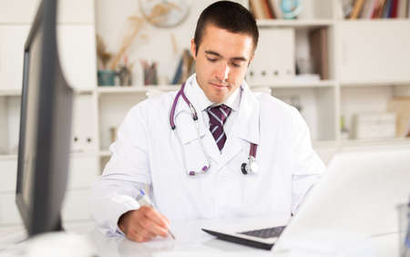 General practitioner working with case histories on laptop