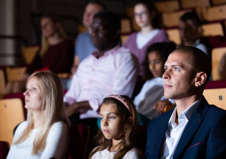 Father, mom and daughter are carefully watching spectacle or concert in theater auditorium