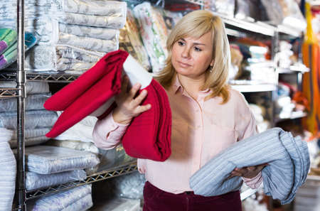 Mature female choosing cotton bedcover in the shop
