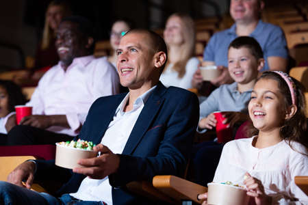 Cheerful family watching a movie and eating popcorn in cinema