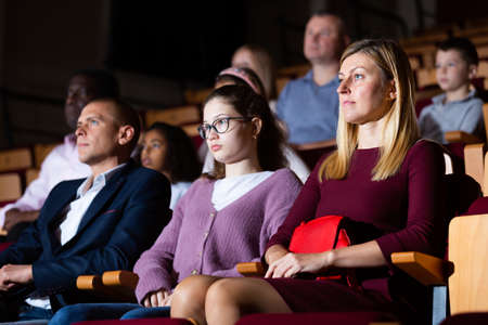 Family couple with teenage daughter watching theatrical performance