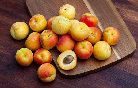 Whole and halved ripe apricots on wooden background