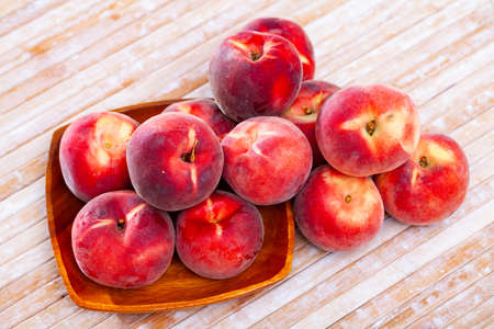 Whole and half fresh red peaches on wooden table.