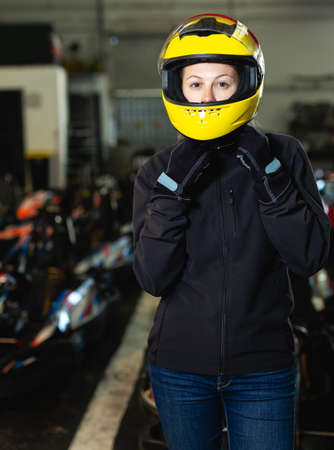 female go-cart racer posing at cart circuit