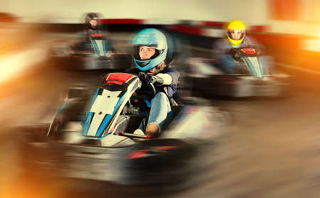 Female racer in helmet driving kart on track