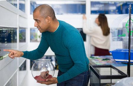 Positive man choosing aquarium fish in shop
