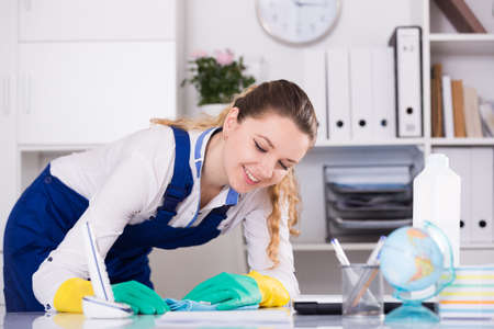 Cheerful female cleaning furniture