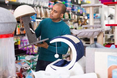Man choosing cat furniture supplies in shop