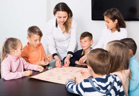 Elementary age concentrated children at table with board game and dice