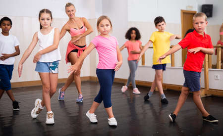 Group of tweens doing dance workout with female coach