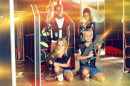 Tween girls and boys with laser pistols posing together