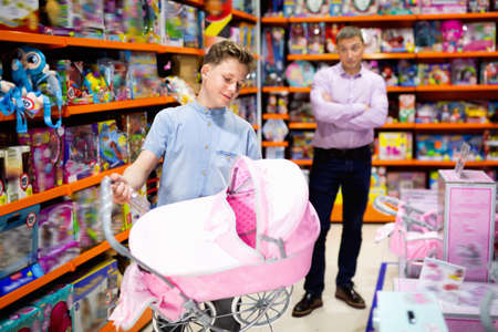 Teen boy choosing pink stroller for dolls in children toy store with adult man dazedly looking at him