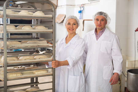 Two bakers near rack trolley with formed dough