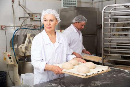 Female baker preparing shaped dough for proofing
