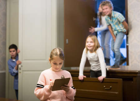 Preteen girl trying to find solution of riddles in quest room