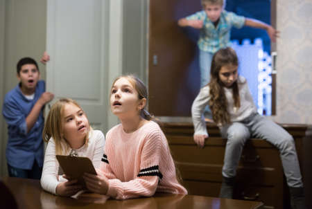 Two preteen girls trying to find solution of riddles in quest room