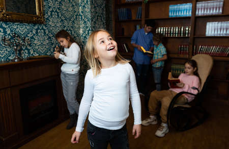 Cheerful preteen girl having fun in quest room with friends