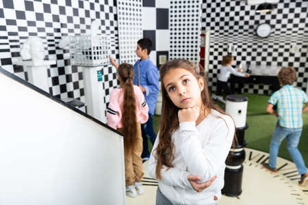 Pensive girl solving conundrum in quest room designed as chessboard Stock Photo