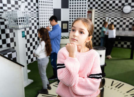 Pensive girl solving conundrum in quest room designed as chessboard