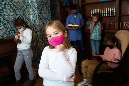 Pensive girl in protective mask solving conundrums in lost room