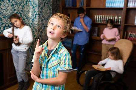 Preteen boy thinking about solving puzzle in escape room Stock Photo
