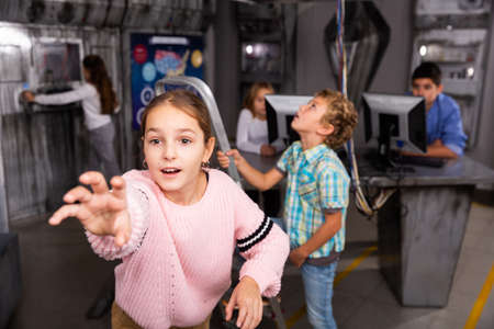 Tween girl holding out hand to something in escape room