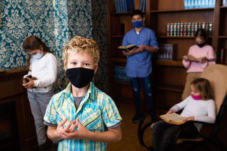 Tween boy in protective mask solving puzzles in escape room