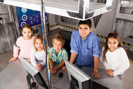 Smiling tweens standing in quest room stylized as bunker Stock Photo