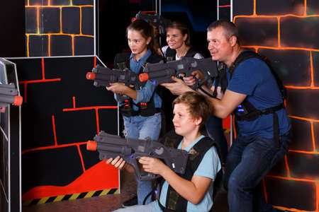 interested young parents and children with laser pistols playing laser tag